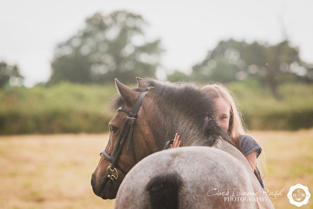 a girl cuddling her pony