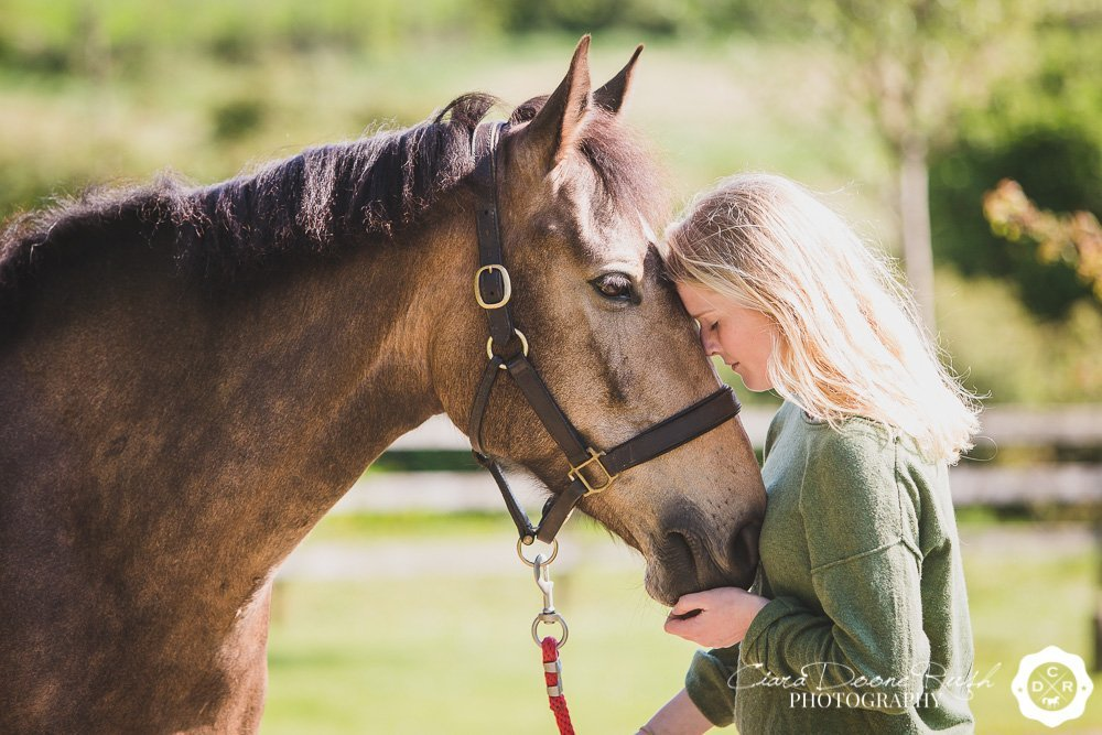 a girl and her horse cuddling on a photo shoot in ireland
