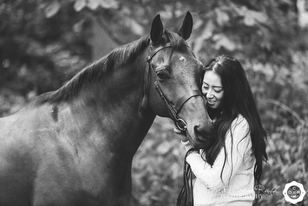 a horse and rider in the woods on a photo shoot
