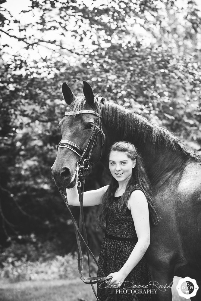 black and white photo of a girl and her horse
