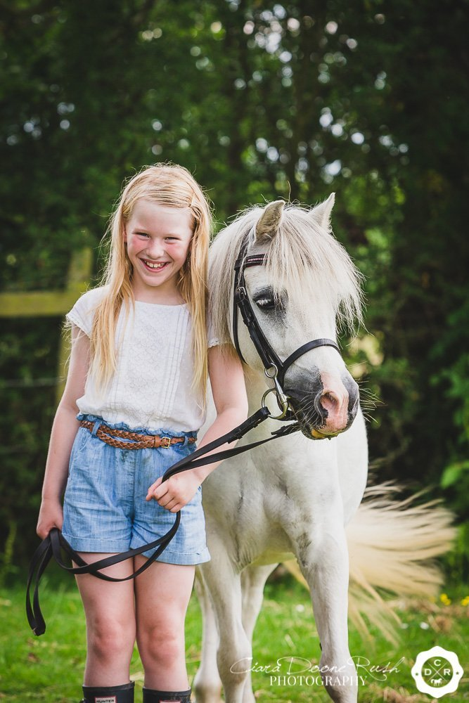 a kid and her pony smiling
