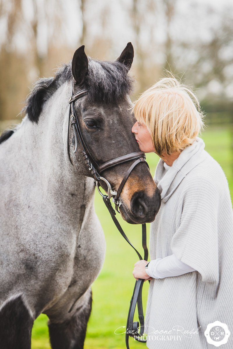 woman giving her pony kisses on a photo shoot