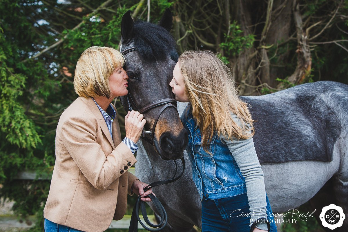 mother and daughter giving their pony kisses