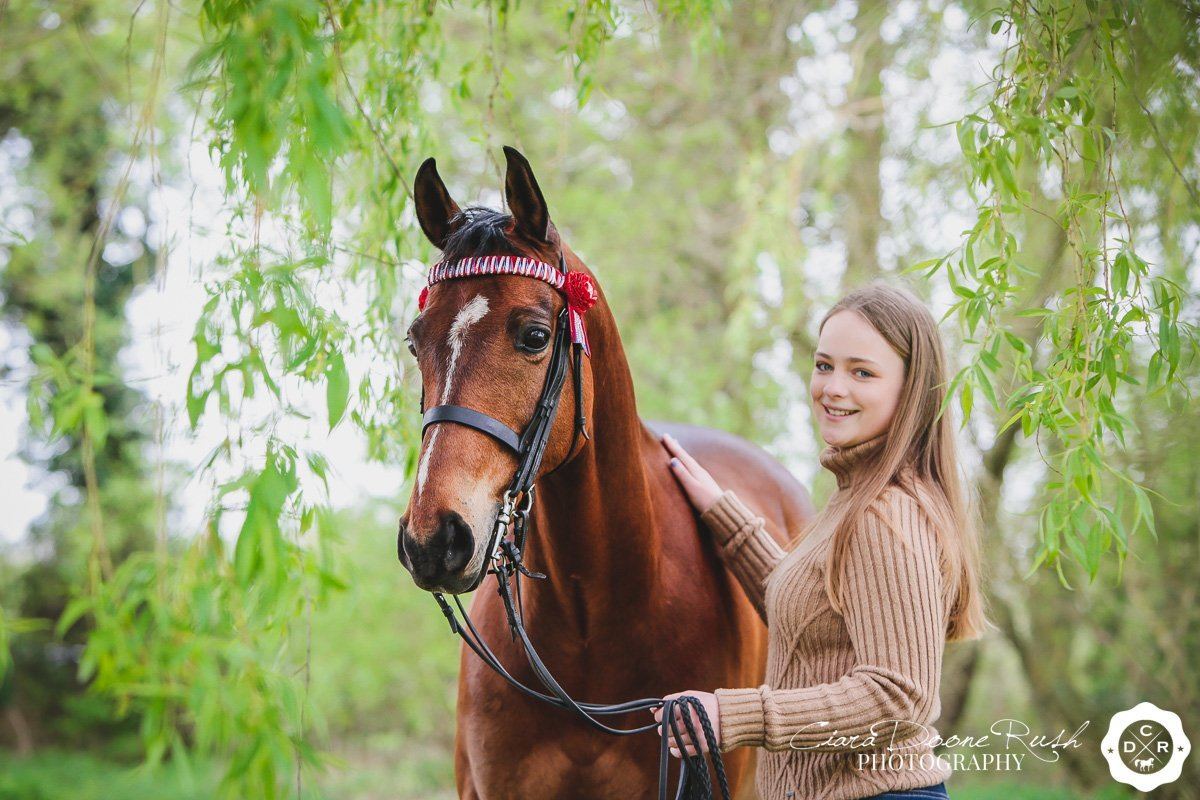 a girl and her pony under a tree