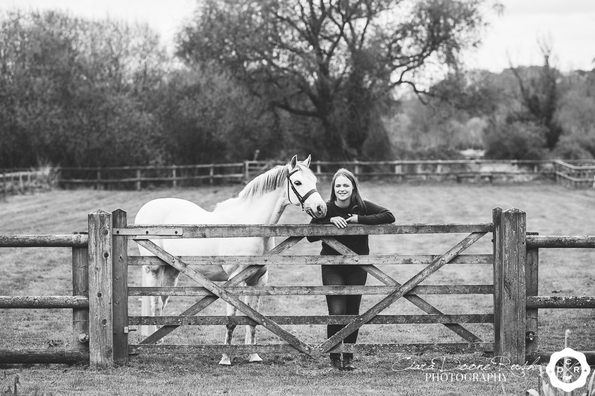 a girl and her pony leaning on a gate