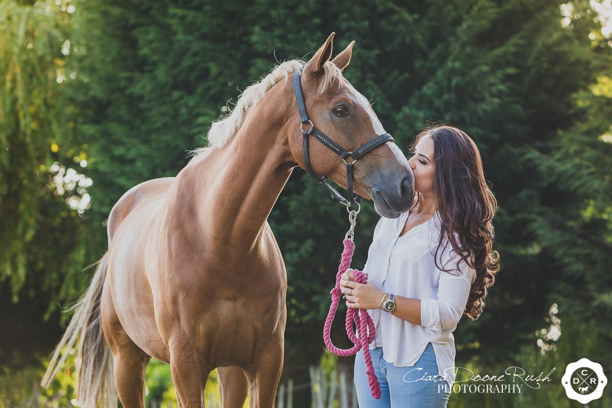 a woman kissing her horse on a summer evening horse and rider photo shoot