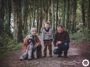 a family and their dog in the woods on a photo shoot