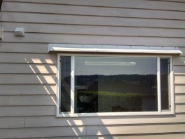 Affordable window awning, canopy or hood mounts above window to stop leaks. Front gutter prevents dripping.