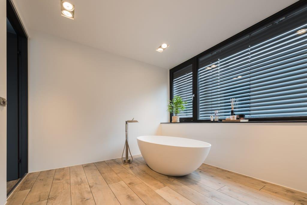 Wit vrijstaand bad in een badkamer uitgebouwd met dakkapel