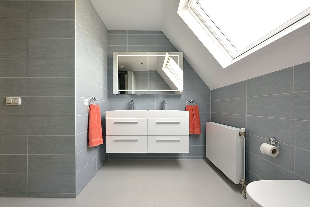 Een badkamer met lichtblauwe groene/blauwe wantegels en witgrijze vloertegels