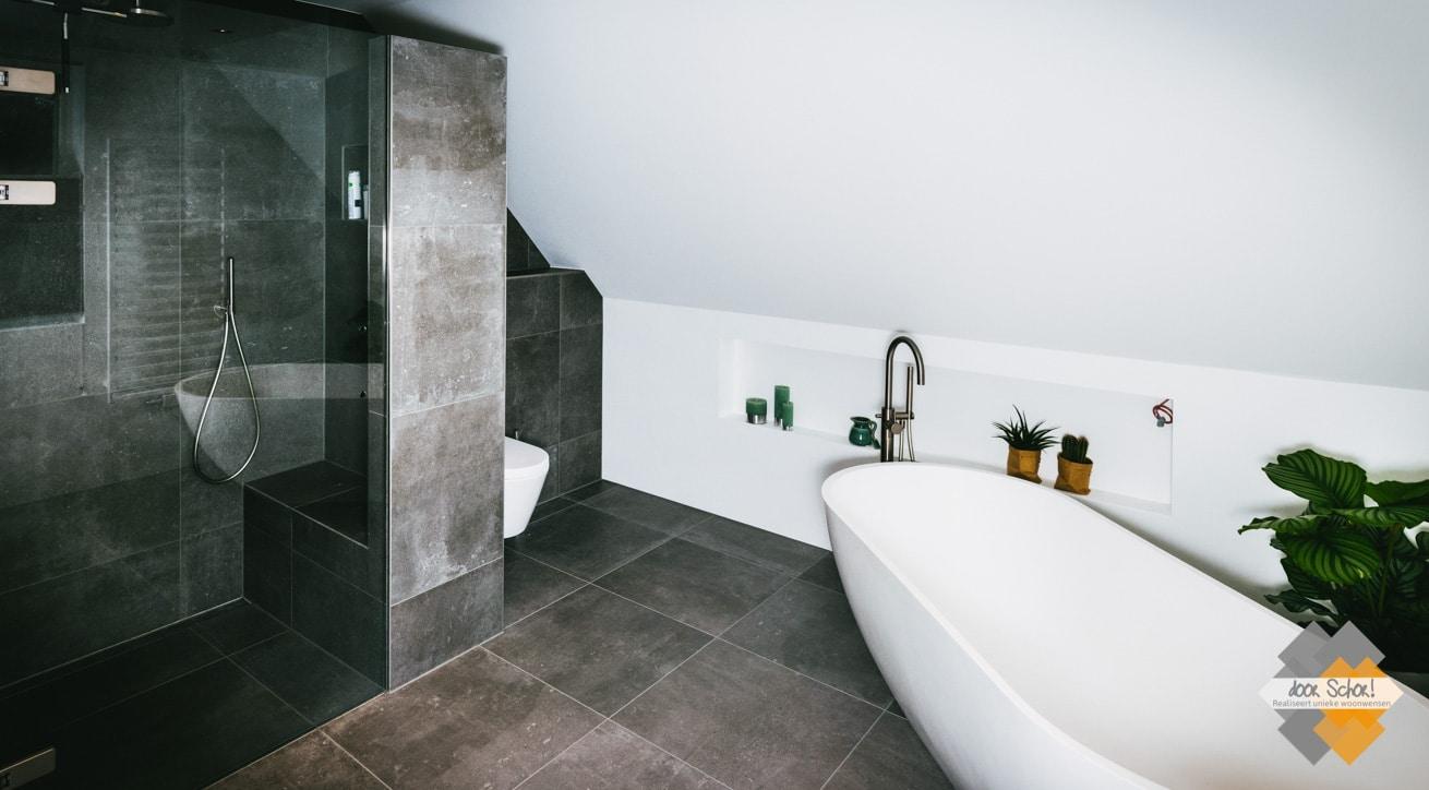 Mooi wit vrijstaande bad met een RVS vrijstaande kraan onder schuin dak