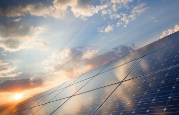 "Clean energy continues to gain momentum — as these technologies improve and develop, the energy economy is making a historical transition. I've noticed more blue and black screen panels popping up on house and business rooftops, and my first thought is always, ""Good for them!"" Then I find myself in a moment of wonder — how do those magic energy boxes actually work? Surprisingly, the idea of solar energy has been around since 1839, when Alexandre Edmond Becquerel discovered that certain materials create electric sparks when struck by light from the sun. Harnessing this energy into PV cells (photovoltaic cells), or solar cells, was discovered later in the 1800s and further described by Einstein in the bloom of twentieth-century physics. A solar panel is a set of solar cells, and each solar cell is like a sandwich. The bread of the sandwich is the two semi-conductive layers of material, typically crystallized silicone. On its own, crystallized silicone isn't a great conductor, so it goes through a process called ""doping"" wherein the silicone crystals are doped with impurities to increase their conductivity. The bottom layer is doped with Boron to bond with a positive charge (P), while the top is doped with Phosphorus and facilitates a negative charge (N). When sunlight enters the cell, the doped silicon layers knock electrons loose. The best part of the sandwich (the jelly between the bread) is called the P-N junction. This is where the mystery and magic happens. The electrons want to flow from the negative layer to the positive layer, but the electrical field in the P-N junction prevents this from happening. The P-N junction forces the electrons to jump from the positive layer to the negative layer within a circuit, creating a flow of electrical current — much like the positive and negative sides of a battery. This flow of electrons is what we know as electricity, powering our lights, computers, phones and vaporizers. One solar sandwich cell only generates a few watts, so they are linked together into a module or panel; these units can also be grouped together into a larger system called and array — or maybe it should be called a buffet? — of solar sandwiches. These groups are wired to an external circuit, which harvests a supply of electricity for immediate use or excess reserves to flow and integrate back into the grid. A large benefit of solar power is that it is harvested when and directly where power is needed, helping to meet peak demands of energy on the grid. A great example are those muggy, lethargic days where everyone has their AC on arctic full blast. Those are perfect days for solar panels to kick in and supplement the grid. This on-site generation also reduces the chance of a loss of electricity through the transmission of electrical currents from a distant power source. Have you ever stood near or beneath a transmission tower and heard that fuzzy snapping sound? That eerie crackle is an audible expression of lost electricity. You may have also noticed that on hot days, power lines may sag more than usual. This is not only a result of gravity, but heat causing expansion in the lines and making them droop. Unlike traditional power plants, which result in large failures if only a part of the system is damaged, a large solar system will continue to harness and produce electricity even if a section is damaged. The largest benefit of solar energy, however, is that it is 100% clean and renewable. A challenge of current solar power technology is having energy flowing from customers rather than to them. This is a sticky situation for utility companies. If a community can create more energy than they use, the ""feeder"" lines running from the community to the utility may not be capable to handle the flow of electricity in the opposing direction. This challenges grid operators, as they can no longer control the fluctuations and output of the system, creating instability on the grid. Solar is also dependent on the weather; condition changes can drastically influence the amount of energy being produced. Additionally, large-scale solar arrays situated far from urban centers also face a loss of energy through transmission, just as non-renewable energy sources do. These challenges are only a piece of the puzzle of our future energy economy. As we have already seen, as technology rapidly develops, it adapts to human needs; we need only to continue seeking solutions for storage and grid stability."