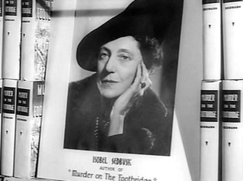 Scena dal film Il Sospetto dove vediamo il retro di un libro giallo intitolato La morte ha il cuore caldo, dell'autrice Isobel Sedbusk