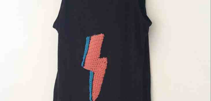 black vest with Bowie colours crochet lightning bolt embellished hanging on white wall