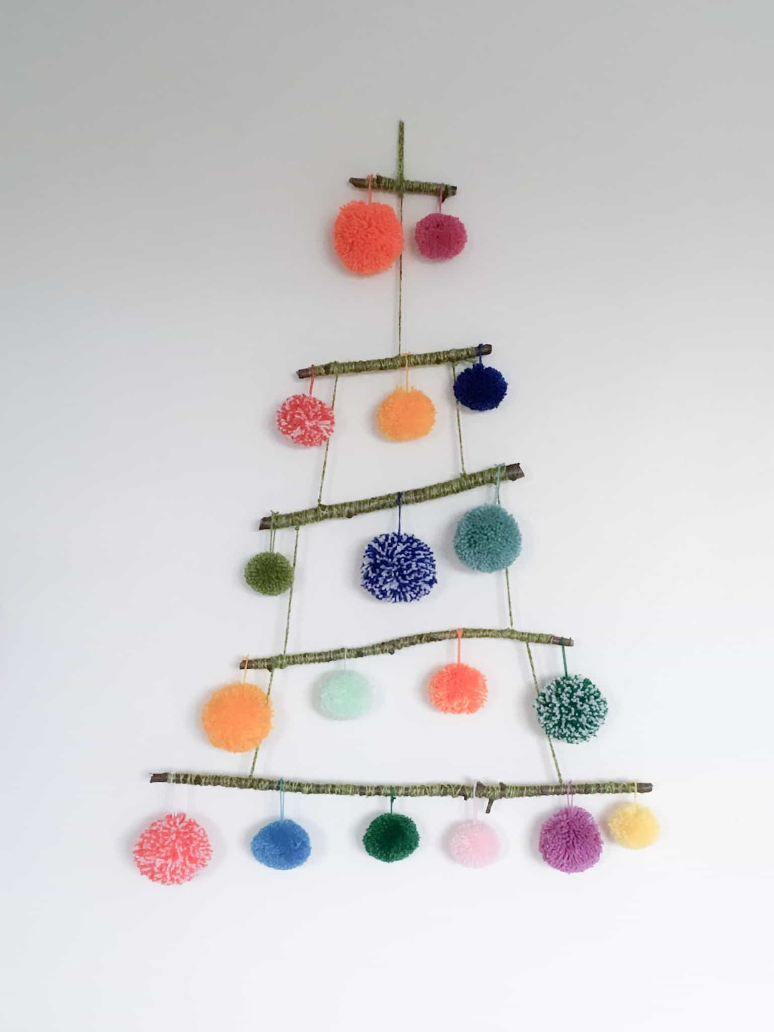 Coloured pom poms hanging from horizontal sticks to make an alternative christmas tree or wall decoration