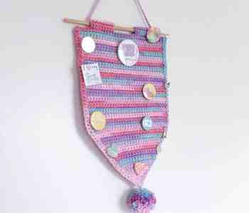 crochet pennant banner with pom-pom displaying enamel pins and badges