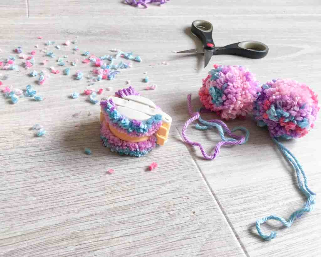 pom pom maker with pom poms, scissors and fluff