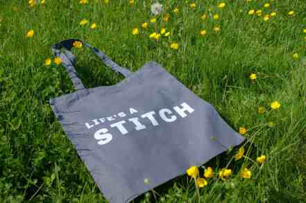 Life'S a stitch slogan tote bag in grey on buttercup meadow