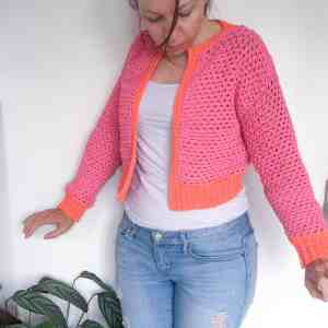 Woman in pink and orange crochet cardigan standing against white wall