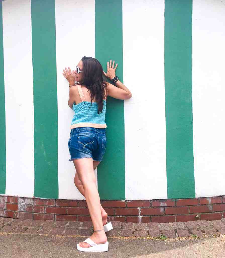 girl modelling cotton summer crochet top in front of green and white striped building