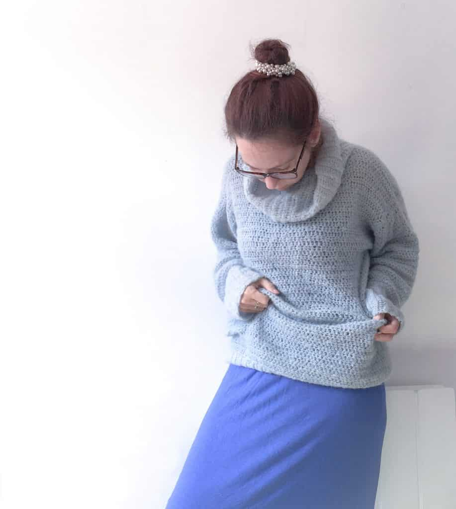 Woman in blue cosy crochet alpaca silk roll neck sweater stepping over something