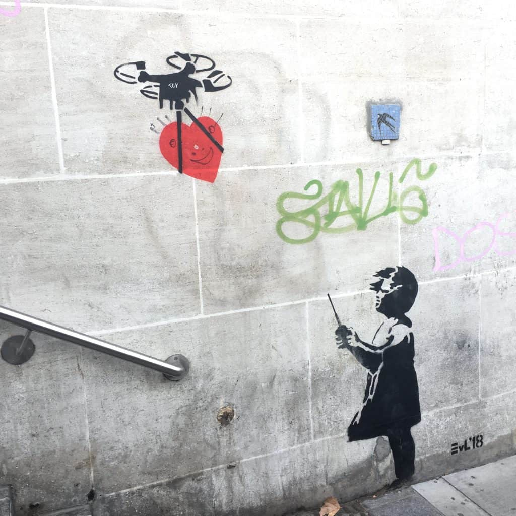 Graffiti girl flying drone by Banksy