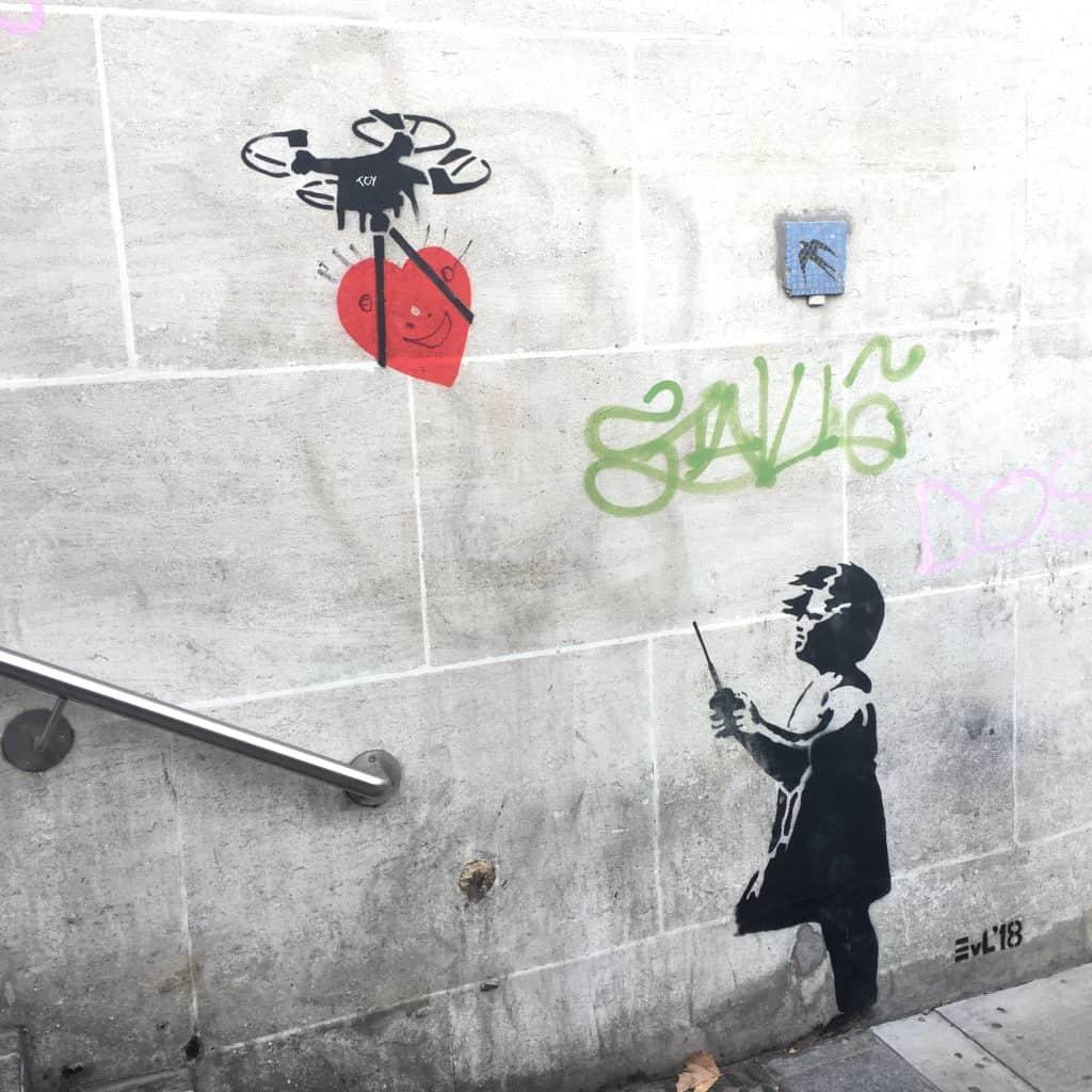 Graffiti girl flying drone by Banksy
