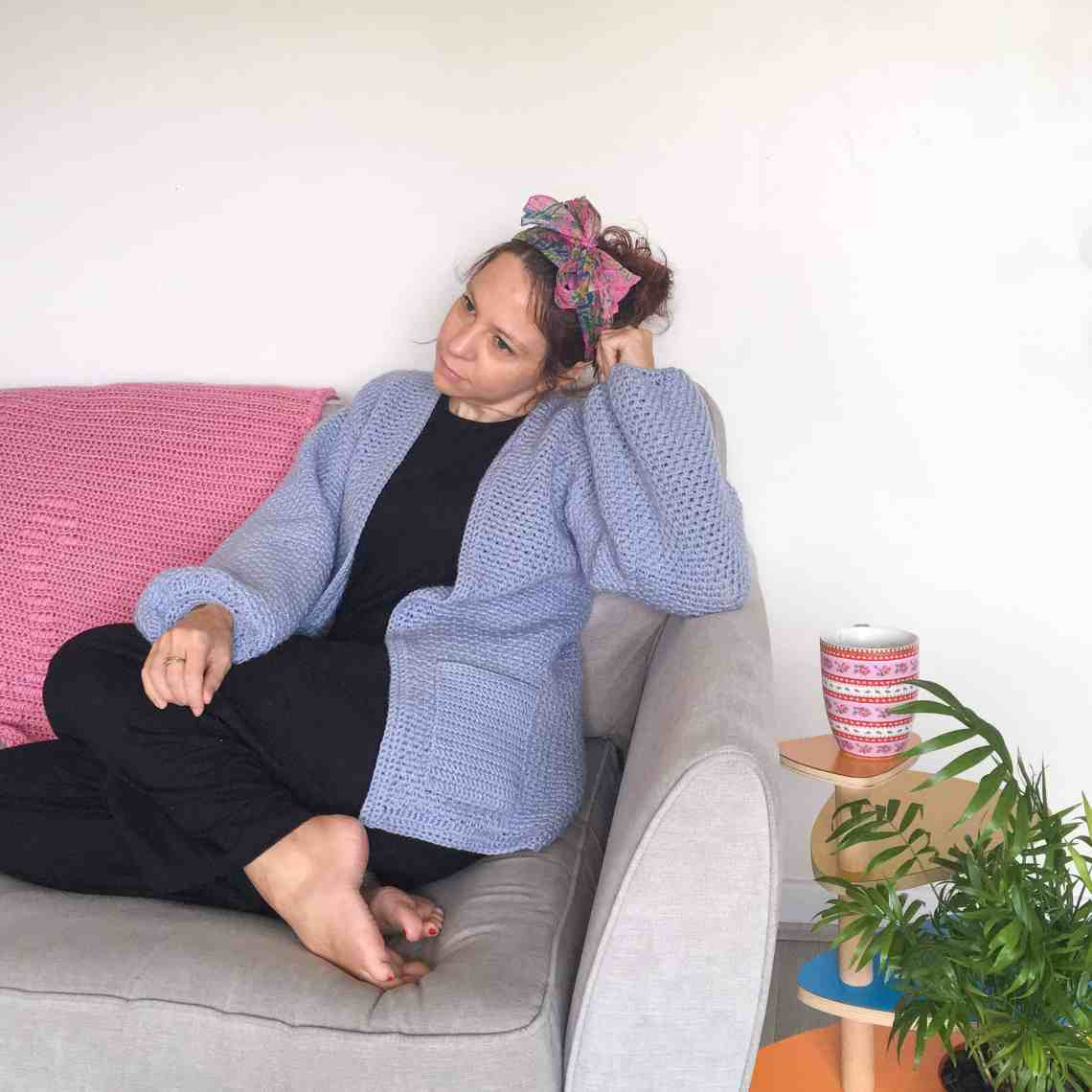 Girl on sofa wearing crochet cardigan and headband