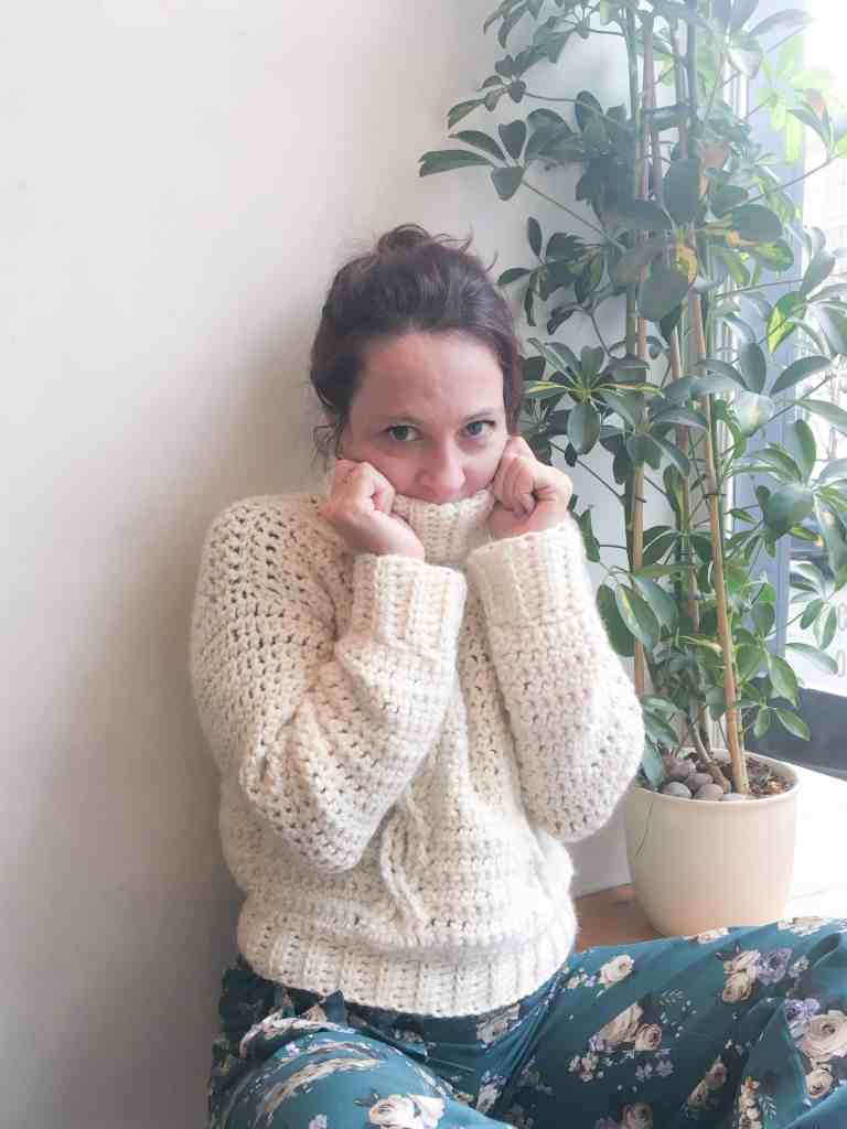 Girl in cable knit crochet jumper pulling hiding