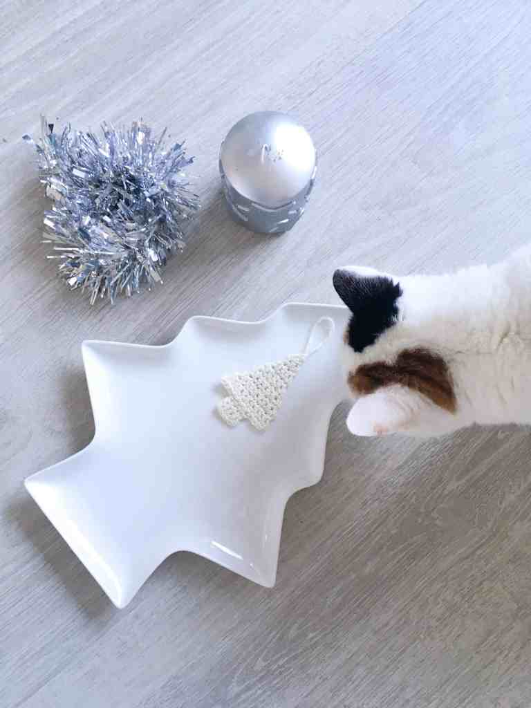 cat looking at crochet christmas tree decoration on tree plate