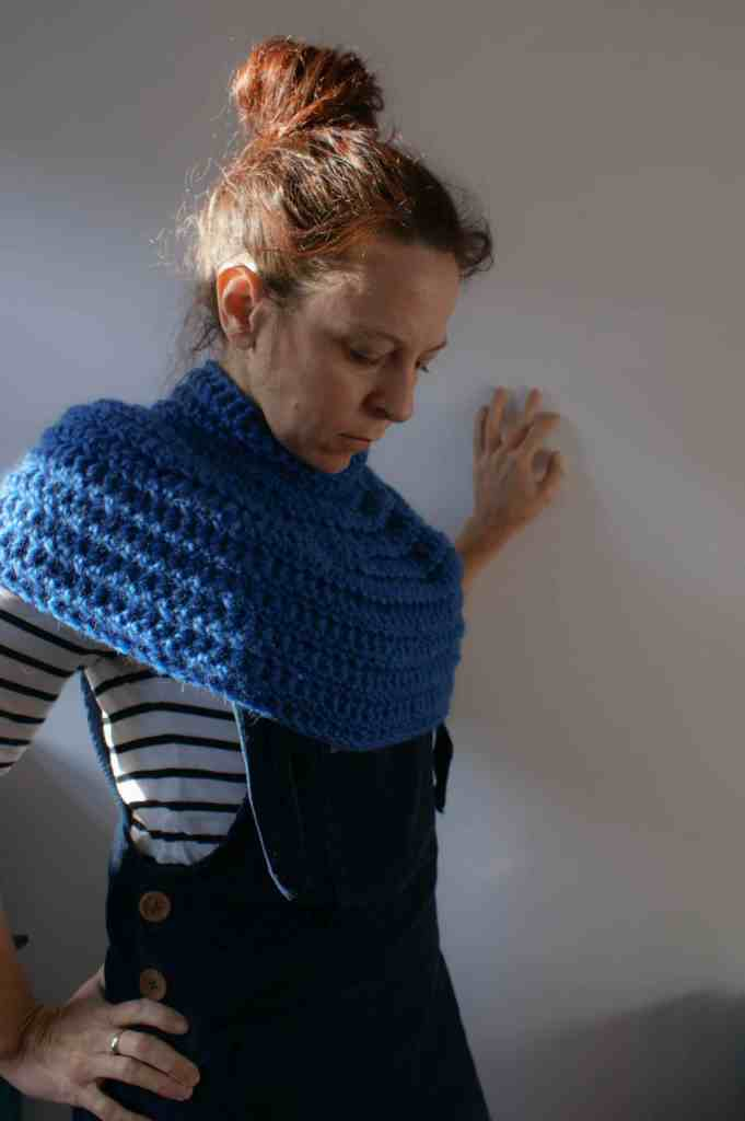 Woman in striped top Blue crochet cowl poncho