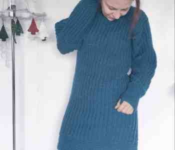Girl tucking hair wearing teal crochet dress