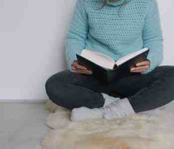 Woman crossed legged reading wearing crochet sweater