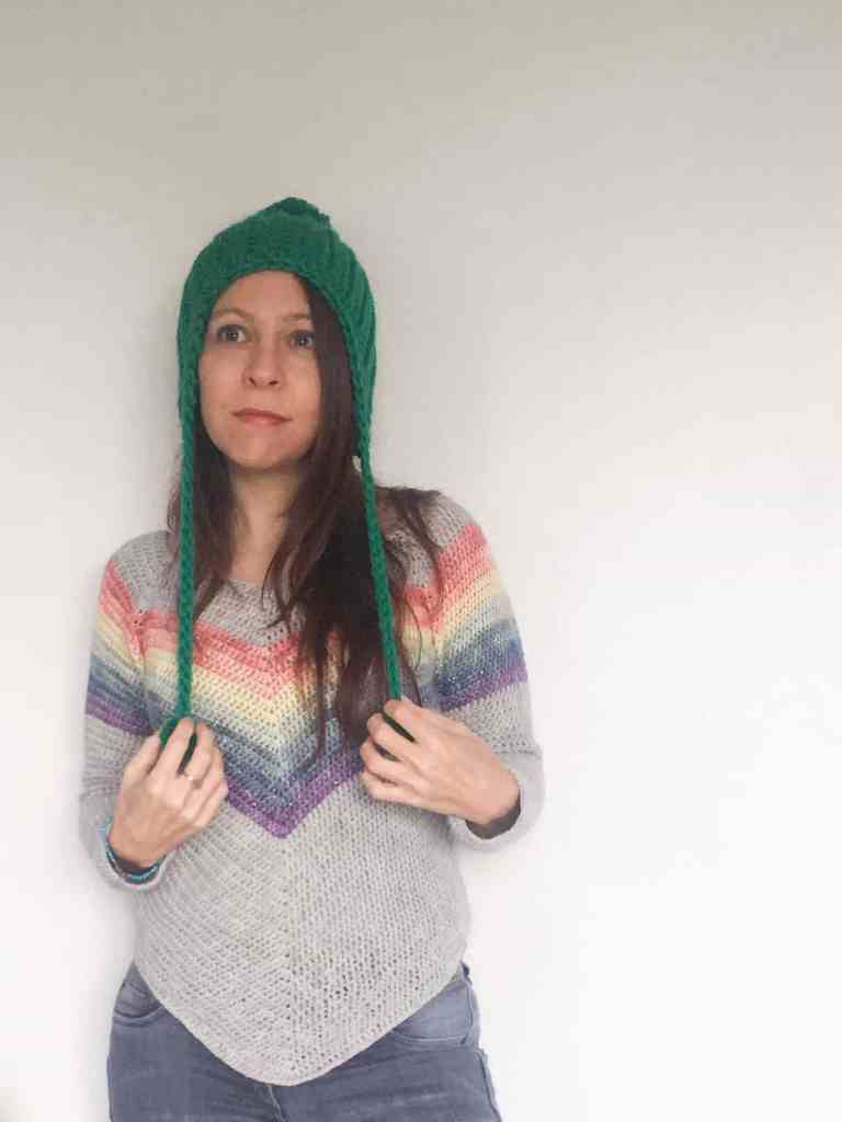 Woman in green crochet hat with pom poms and rainbow stripe crochet sweater