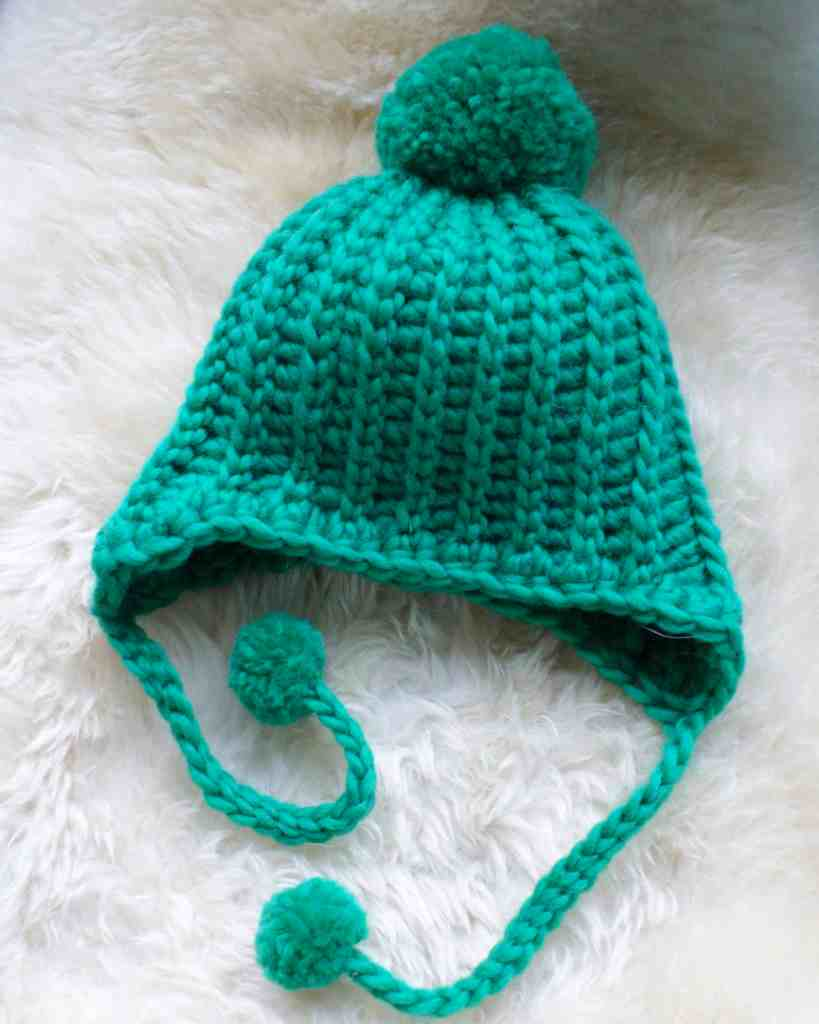 Crochet hat with ear flaps and pom poms