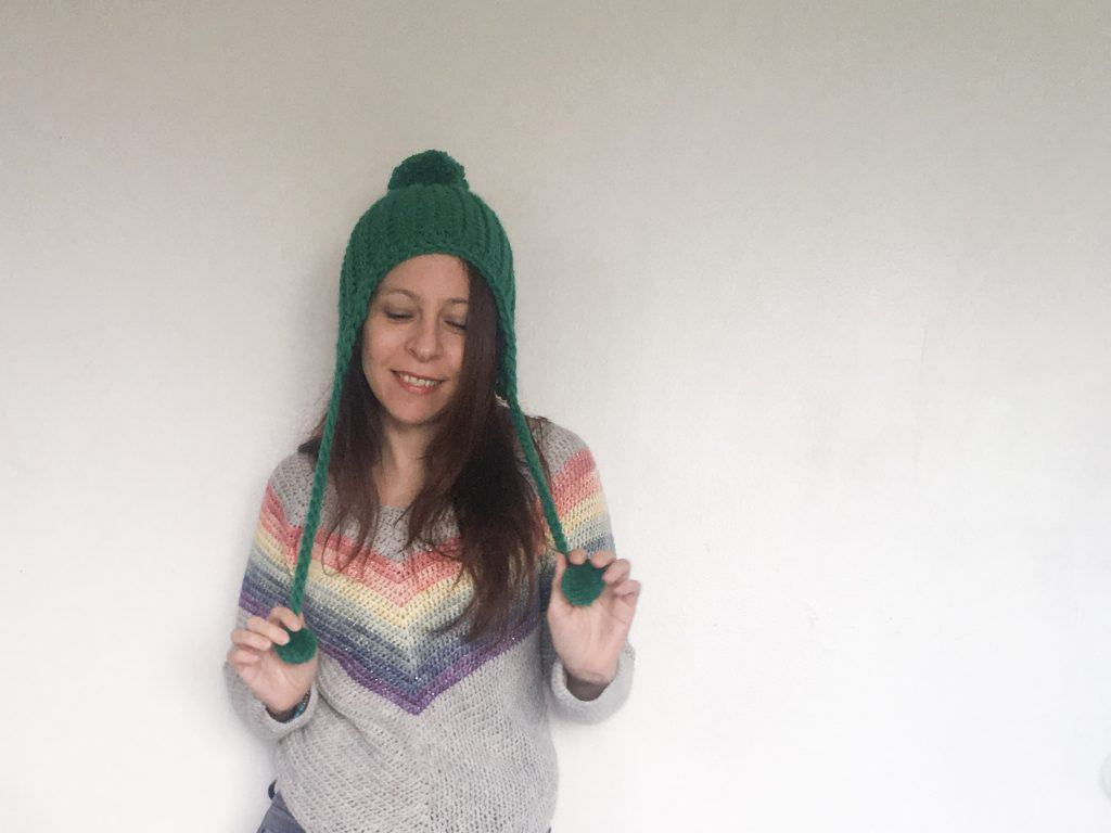 Woman in rainbow sweater and green crochet hat