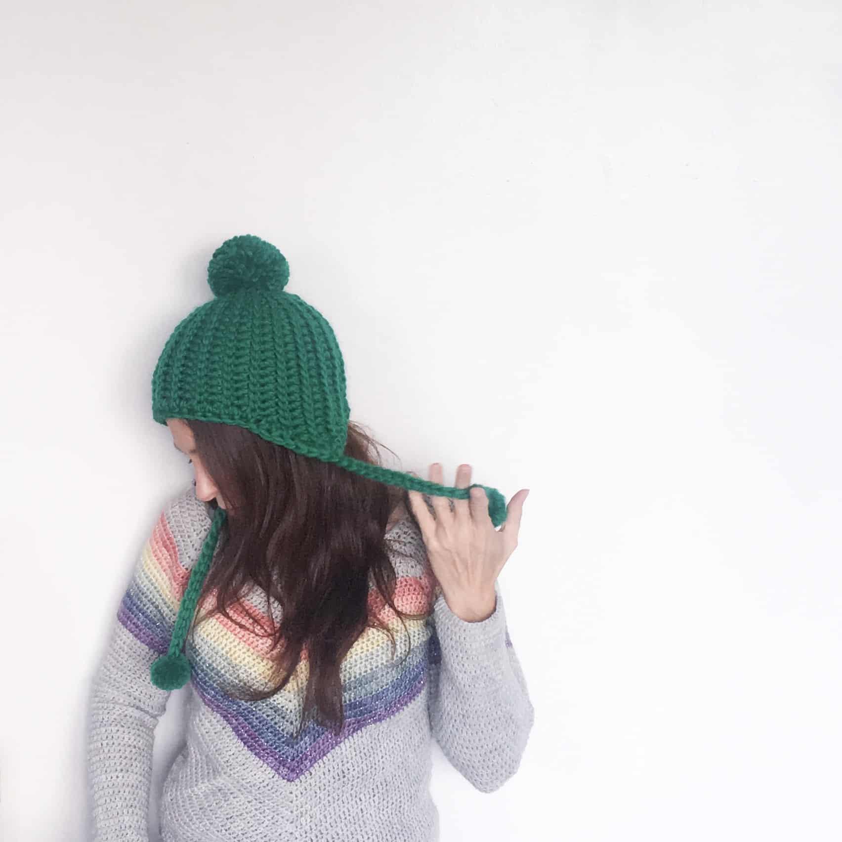 Side view of green crochet pom pom hat
