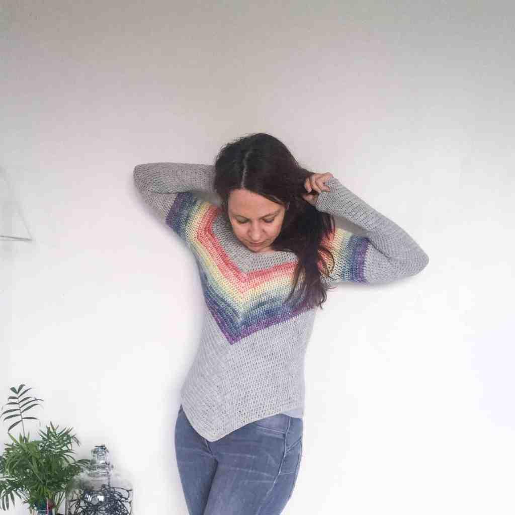 Woman wearing rainbow crochet sweater holding hair