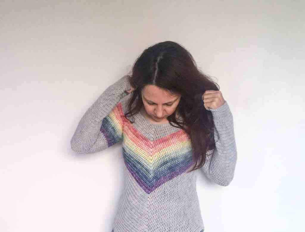 Woman in sparkly rainbow striped crochet sweater