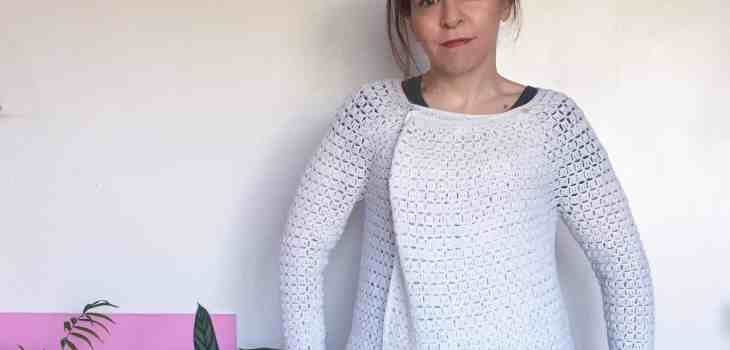 Woman in white crochet cardigan against white wall