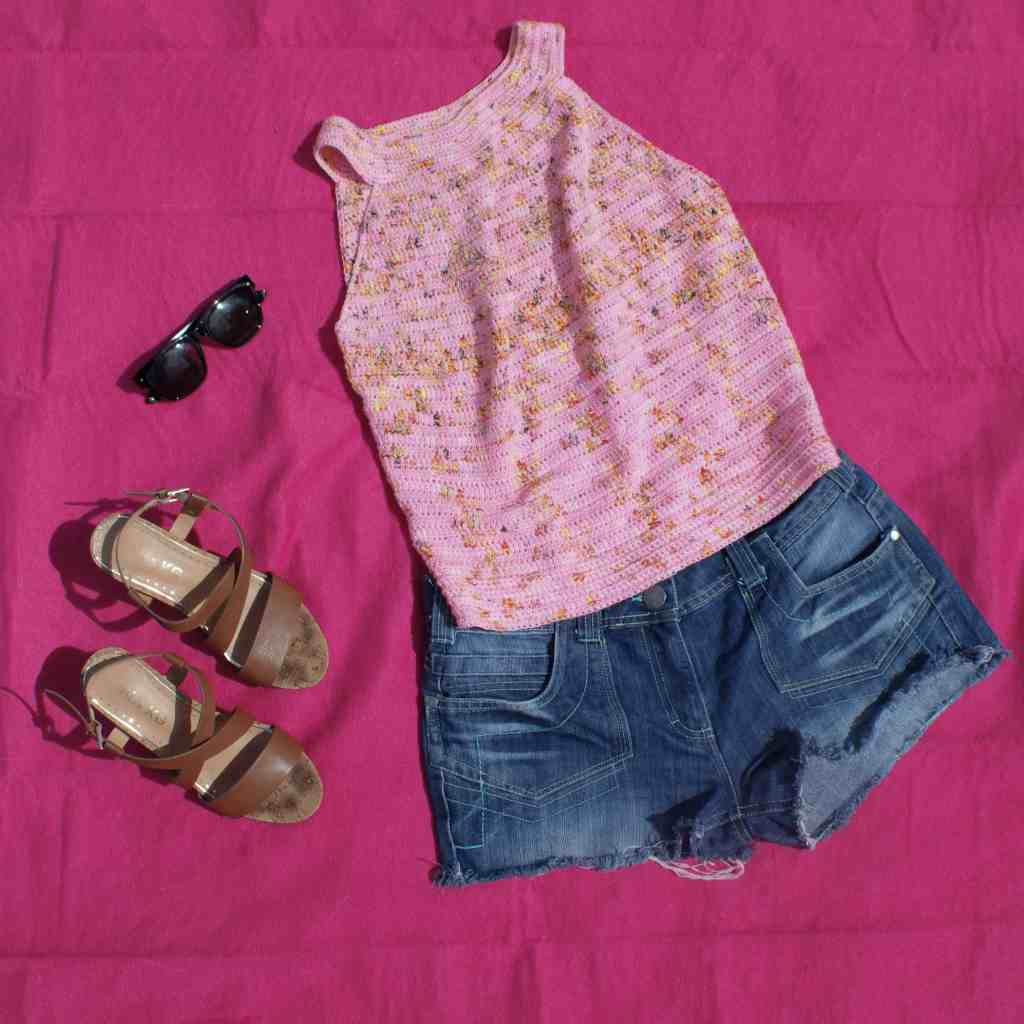 light pink crochet summer vest top lying on a fascia blanket with black sunglasses denim shorts and brown wedge sandals