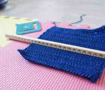 Blue Crochet swatch on pink mat with ruler and tension measure