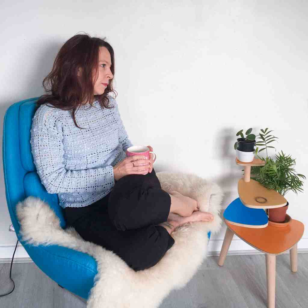 Woman sitting in chair in geometric blue crochet sweater