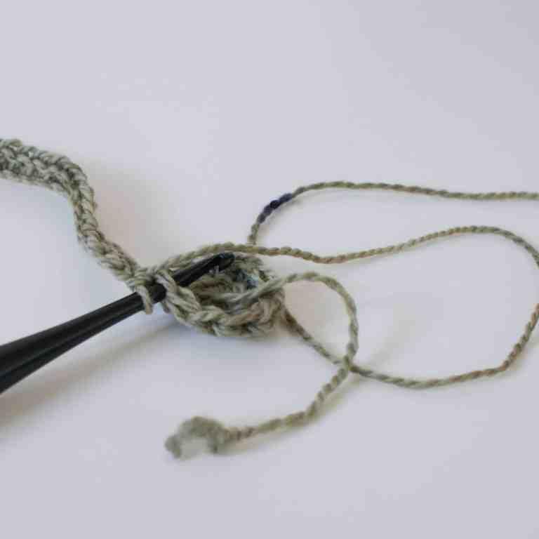 Black Crochet hook and green yarn making crochet hat