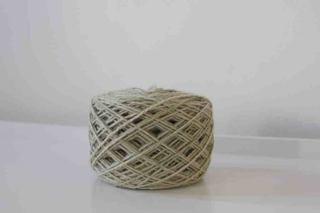 light green yarn cake on white surface