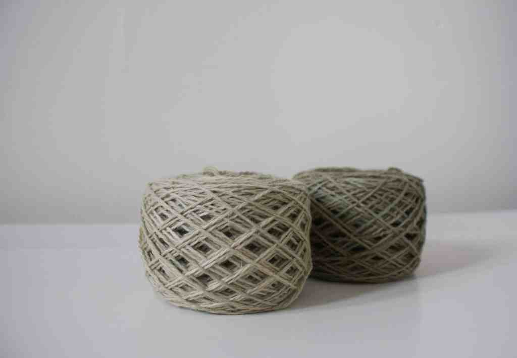 two cakes of yarn on white surface one light green one dark green
