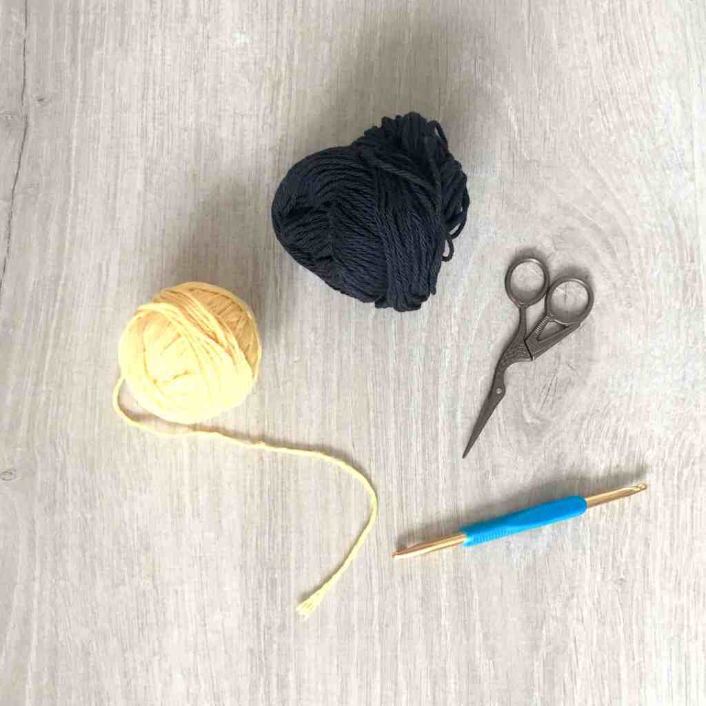 Yellow and black cotton yarn with two ended crochet hook with scissors