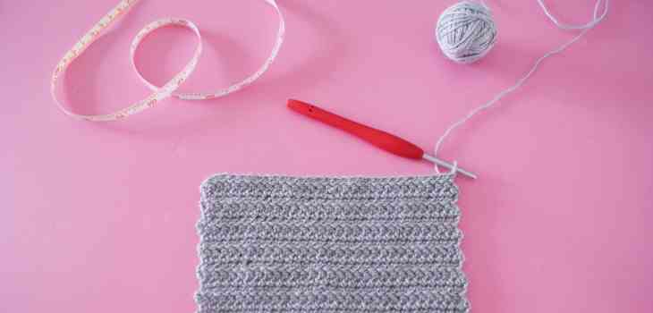 Grey herringbone crochet swatch on pink background with red hook, ball of yarn and tape measure
