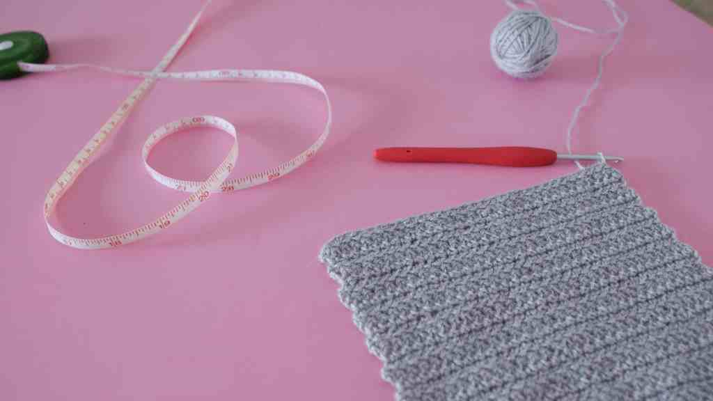 Crochet swatch on pink background with crochet hook, ball of yarn and tape measure