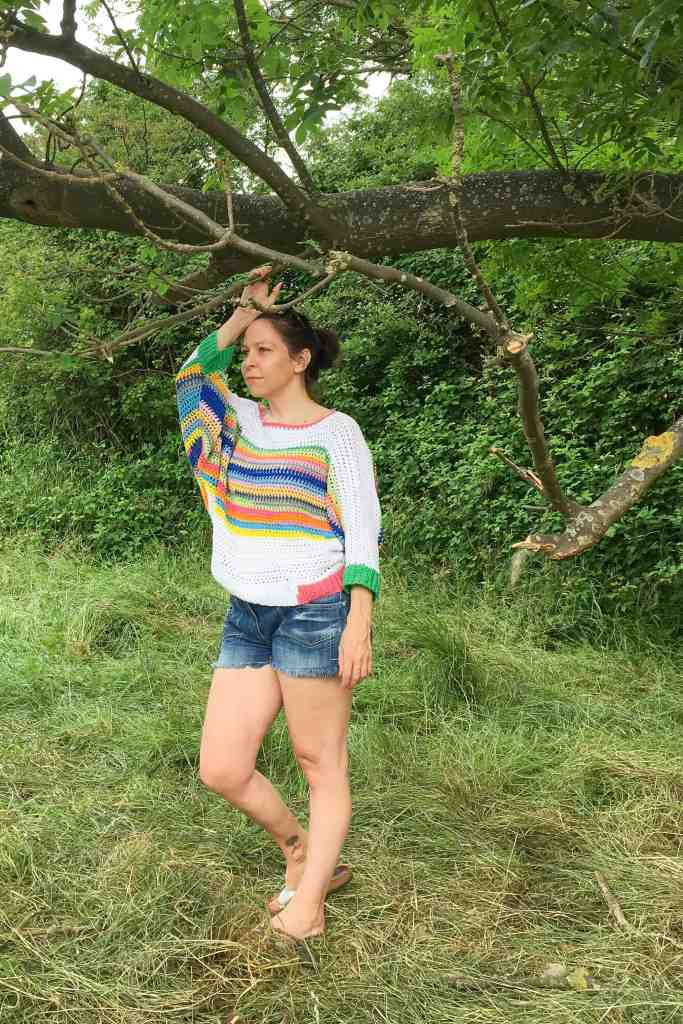 Woman wearing shorts and rainbow striped crochet sweater standing in meadow with hand holding tree branch
